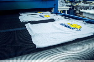 Row of screen printed shirts coming off a belt dryer.